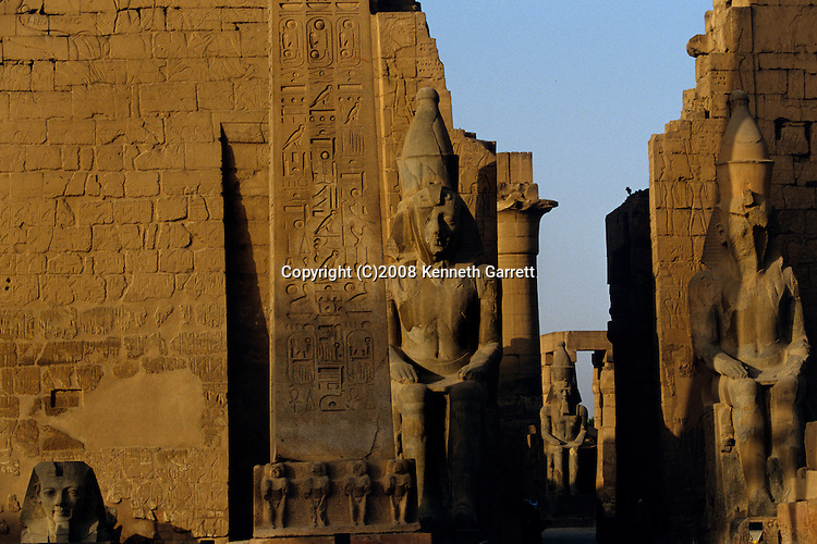 Colossal statue of Ramses II (the Great) , in front of pylon, Temple of Luxor, Festival of Opet, Thebes, Egypt, red granite obelisk, pylon depicts Battle of Kadesh, Hittites