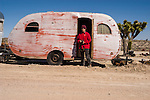 Faded red canned ham travel trailers abandoned by junk yard, Goldfield, Nev.