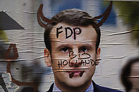 "France. Ile de France. Paris. Partially torn campaign poster of French presidential election candidate Emmanuel Macron for the centrist party ""En Marche"". A graffiti with the written words, Baby from french president François Hollande, and a drawing with two horns. 22.04.17 © 2017 Didier Ruef"