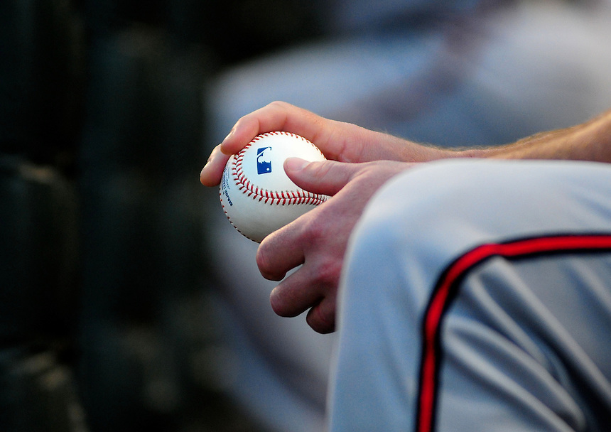 July 9, 2009: Braves pitcher Derek Lowe handles a baseball in the dugout during a regular season game between the Atlanta Braves and the Colorado Rockies at Coors Field in Denver, Colorado.