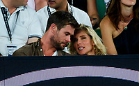 Chris Hemsworth and his wife Elsa Pataky watch Roger Federer of Switzerland and Marin Cilic of Croatia in action on Day 14 of the Australian Open