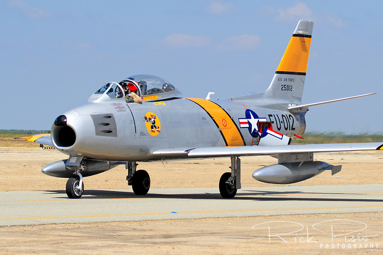 The Planes of Fame F-86 Sabre is taxied across the ramp by Steve Hinton upon arrival to the 2007 Warbirds in Action airshow at Minter Field near Bakersfield, California. The swept wing F-86 is a 50's era Air Force fighter that was known for its ability to dogfight against the Russian built Mig-15 during the Korean War. Designed by North American Aviation, and first introduced to the Air Force in 1949, there were a total of 9,860 of the f-86 fighter and its variants built.