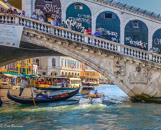 Regatta Day, decorated boats of every kind passing under the Rialto Bridge on the Grand Canal. Venice, Italy