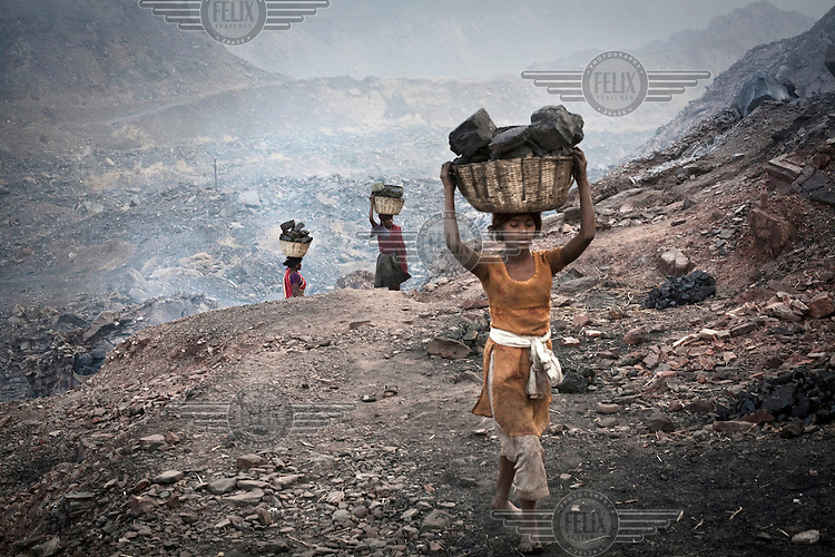Women carrying out coal from an open cast mine near Bokapahari village. Coal fires rage just below the surface of the ground, making it too hot to walk with naked feet. Noxious gases spew up from fissures, rendering the environment toxic. Residents who live above the furnace make $2 a day collecting small chunks of coal that they sell to illegal middlemen. One or two houses collapse annually into vast underground caverns left unfilled by abandoned mining operations.