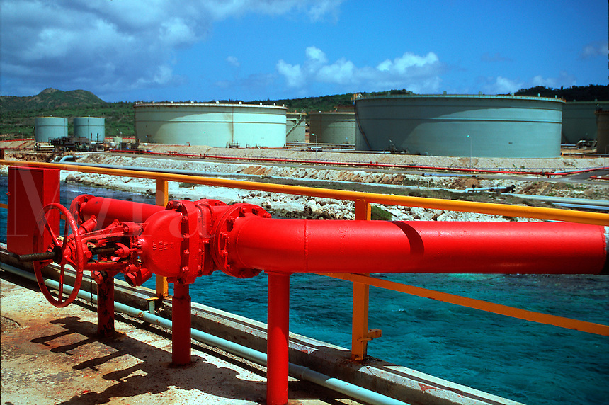 Bright red pipes at an oil storage facility.