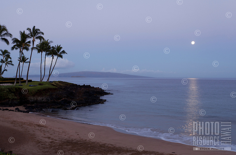 The full moon sets at Ulua Beach, Wailea, Maui, with Kaho'olawe in the distance.