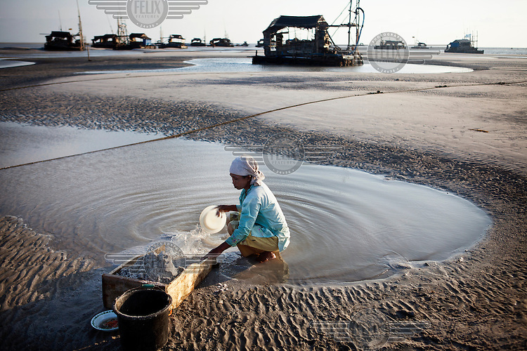A woman pans for tin ore in an abandoned pit. Beyond her are working pits where each wooden rafts supports a diesel-powered suction pump that dredges the sand for tin ore.