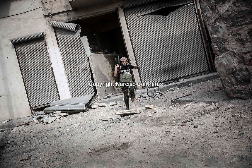 In this Wednesday, Oct. 24, 2012 photo. An rebel fighter runs for cover through the sniper line of fire at the Karmal Jabl front line, northeast of Aleppo City. (AP Photo/Narciso Contreras).
