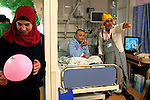 "A Palestinian woman holds a balloon next to Mustafah Mshasha, a Palestinian boy from the Old City of Jerusalem who plays with clown Dudi (Dudy Barashi an Israeli  medical clown who works in Hadassah member of a group call ""Dream Doctor"") as he receives chemotherapy at the Oncology Day Care unit at Hadassah Ein Karem hospital. ..Mustafa suffers from Leukemia and has been treated in the Children Oncology Unit. Photo by Quique Kierszenbaum  .."