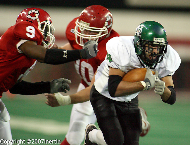 University of North Dakota's Ryan Chappell #4 leaves Byron Bullock #9, and Zach Johnson #90, of the University of South Dakota, grasping for air en route to a touchdown in the first quarter Saturday, Novermber 10, 2007 at the DakotaDome in Vermillion. (photo by Dave Eggen/Inertia)