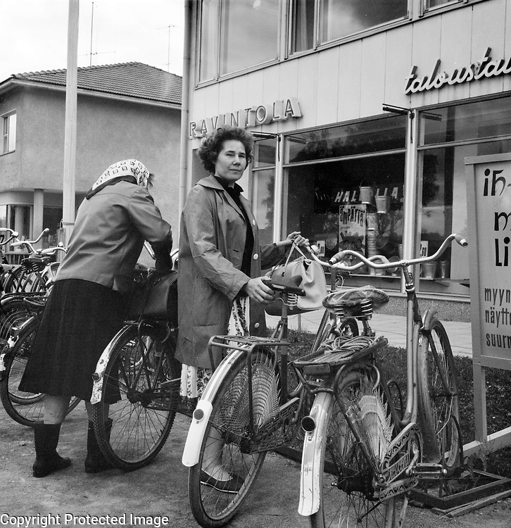 Women with their bicycles outside ship, Finland 1963