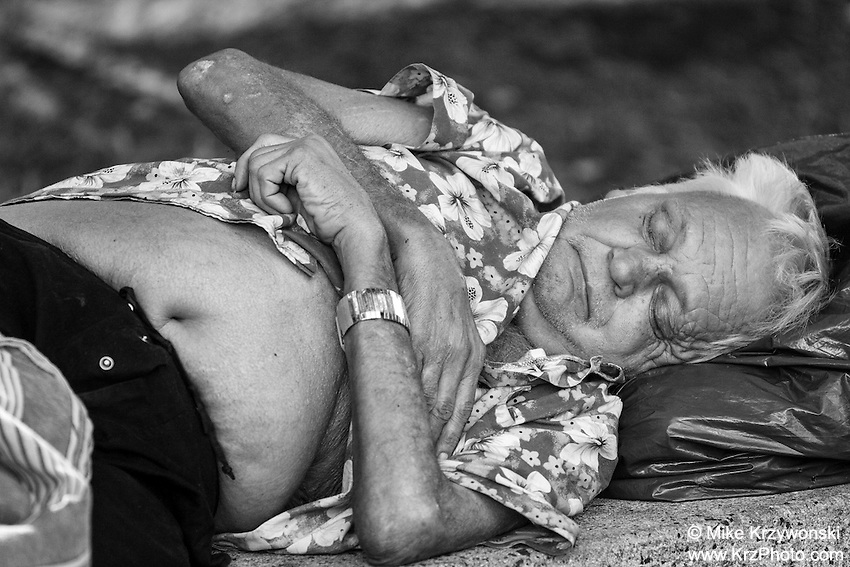 Ederly homeless man sleeping on a bench in Downtown Honolulu, Oahu, Hawaii