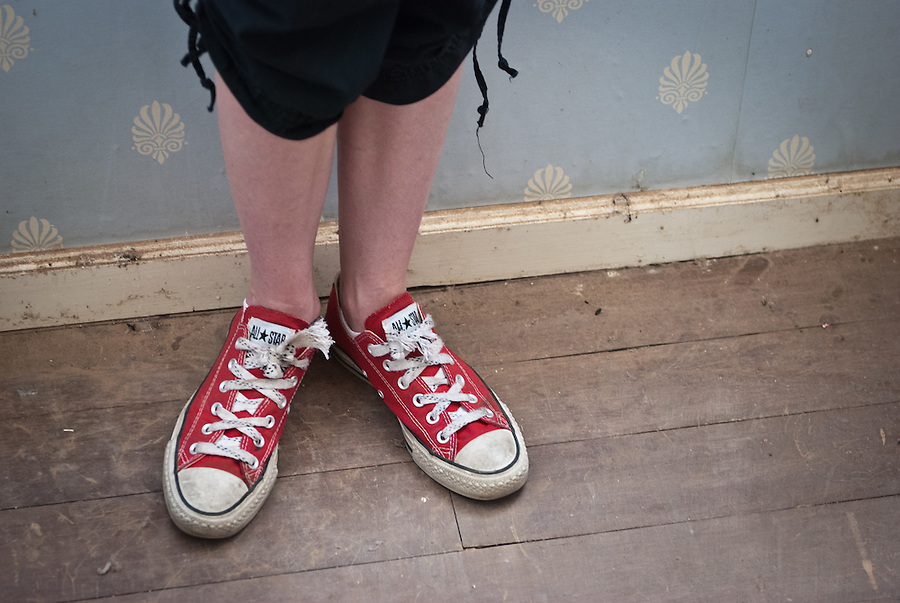 Close-up shot of red Converse shoes worn by a young woman.