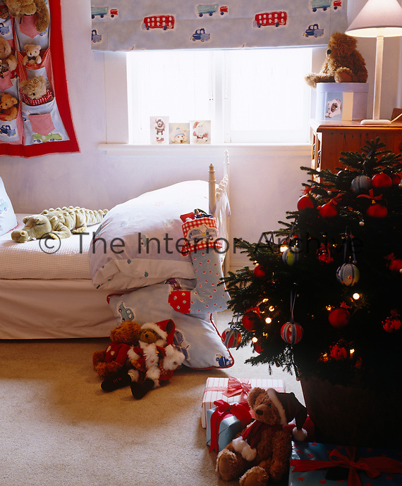 A boy's bedroom is decorated for Christmas with its own tree