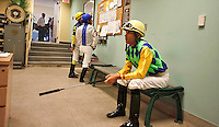 Awaiting the call that will summon the jockeys to the walking ring to meet with trainers and owners before getting a leg up on their mounts.