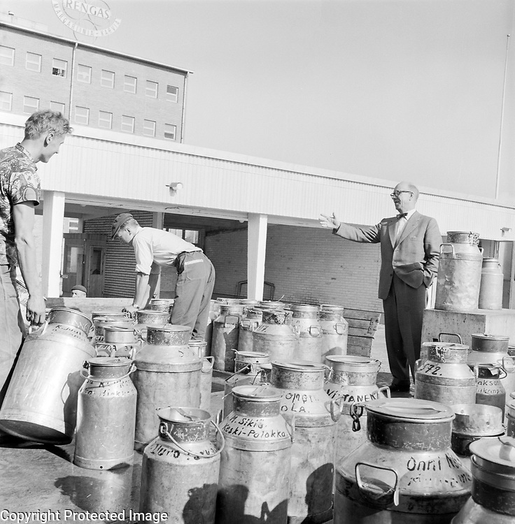 Manager supervising men working on milk churns outside dairy of factory, Finland, 1959