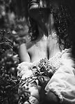 Sensual romantic black and white closeup portrait of rain falling an a beautiful woman chest soaking wet her long dark hair and white summer dress with roses growing in front of her