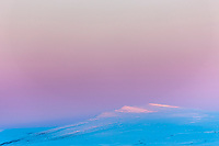 The soft pink and blue hues of dawn fall over the snow covered hills of the arctic coastal plain