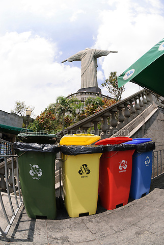 Rio de Janeiro, Brazil, Christo Redentor statue on Corcovado. Four coloured waste bins lined up: green for glass (vidro), yellow for metal, red for plastics (plastico), blue for paper (papel).