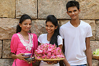TX0822-D. Three young adults with offerings at a temple. Sri Lanka.<br /> Photo Copyright © Brandon Cole. All rights reserved worldwide.  www.brandoncole.com
