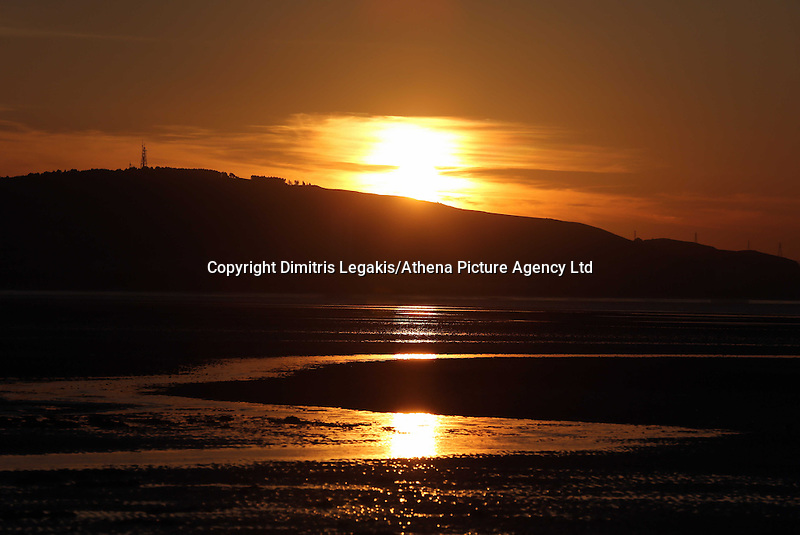 Swansea, UK. Saturday 21 June 2014<br /> Pictured: The sun reflects on the wet sandy beach as it rises over Swansea marking the Summer Solstice and the year's longest day.