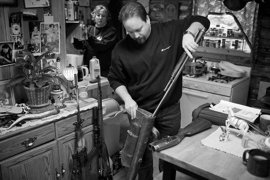 Jeff Stankiewicz, Commander of the Idaho Light Foot Militia, organizes a few of his guns in his small cabin home outside of Naples, Idaho while wife Leslie Brown-Stankiewicz cooks lunch...Stankiewicz claims to own more than a dozen guns, ranging from antiques to assault rifles.