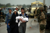 A man holding a baby walks past the US Marines checkpoint near the Tigris River crossing where all the locals who had fled the city were now trying to get back into Tikrit.