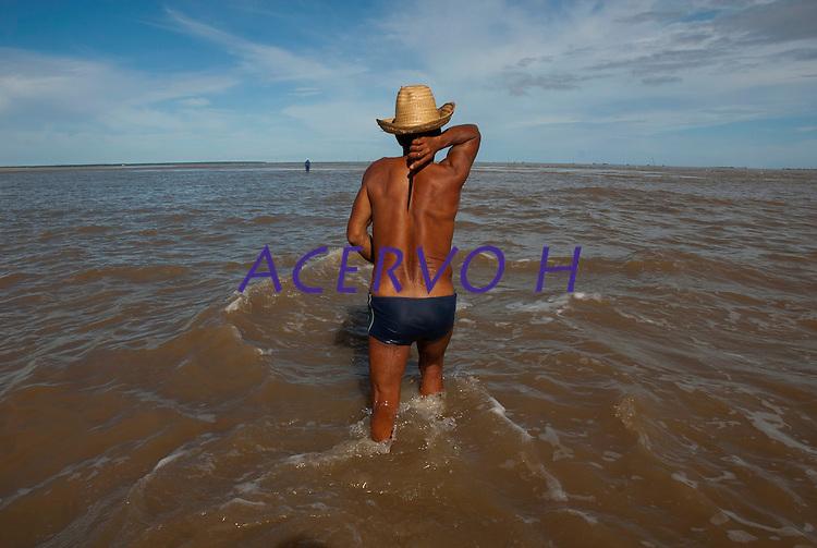 O pescador artesanal Raimundo Ferreira da Silva, 51, (sunga azul), conhecido como Cambeua, pesca com companheiros na Reserva Extrativista Marinha Mãe Grande no litoral do Pará, na foz do rio Amazonas. Os pescadores capturaram por dia cerca de 200 quilos de pescado de várias espécies como: piramutabas, sardinhas, filhotes, pescada amarela, robalo e tainhas.<br />  Curuçá, Pará, Brasil<br />  Foto: Paulo Santos <br />  17/05/2009