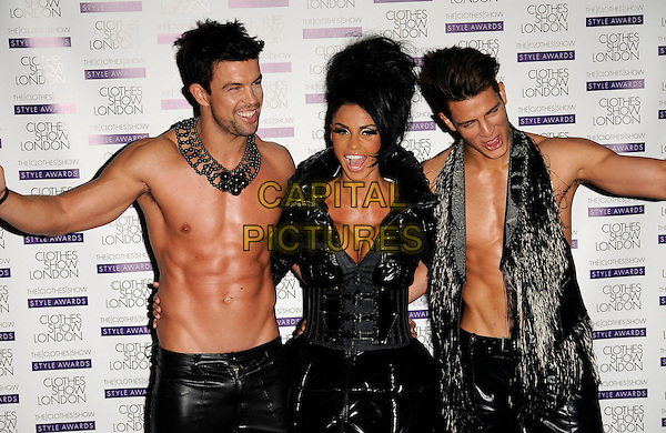 KATIE PRICE aka Jordan & male models .At The Clothes Show London, Excel centre, Royal Victoria Dock, London, England, UK, May 29th 2009..half length black leather trousers pvc dress bondage necklace topless chest cleavage buckles funny smiling mouth open tanned .CAP/CAN.©Can Nguyen/Capital Pictures