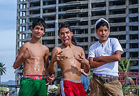 Urban Street Photograph of Three Mexican boys posing for the camera on the beach in Mexico.