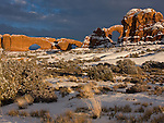Three arches after a winter snow storm, with the North Window, South Window, and Turret Arch lit by the setting sun after a snow in Arches National Park near Moab, Utah, USA.