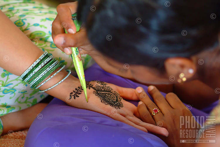 Woman receiving a mendhi ( henna dye ) design  on her hand prior to her indian wedding ceremony