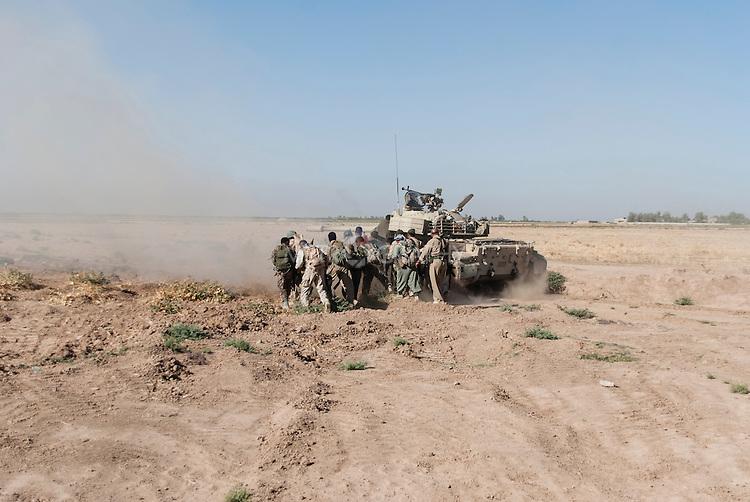 30/09/14  Iraq -- Daquq, Iraq -- Peshmerga fighters advance toward ISIS position behind the tank at the front line in Wahda village, Daquq.