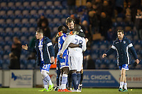 Goalkeeper Sam Walker of Colchester United embraces goalscorer George Elokobi of Colchester United & Adebayo Akinfenwa of Wycombe Wanderers at full time after the Sky Bet League 2 match between Colchester United and Wycombe Wanderers at the Weston Homes Community Stadium, Colchester, England on 21 February 2017. Photo by Andy Rowland / PRiME Media Images.