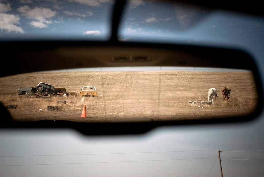 View in the rearview mirror of my car leaving Pine Ridge Indian Reservation. Abandoned cars and horses are trademarks of life on the Rez...