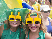 Two youg women wear sunglasses with a middle finger raised in protest. Rio de Janeiro, Brazil. Demonstration against President Rousseff.