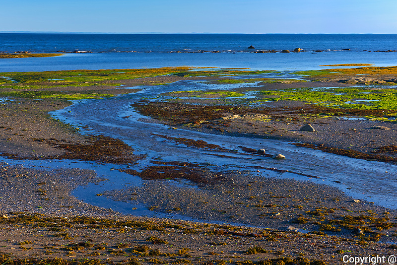 Sunset on rocky shore of St. Lawrence River at low tide<br />