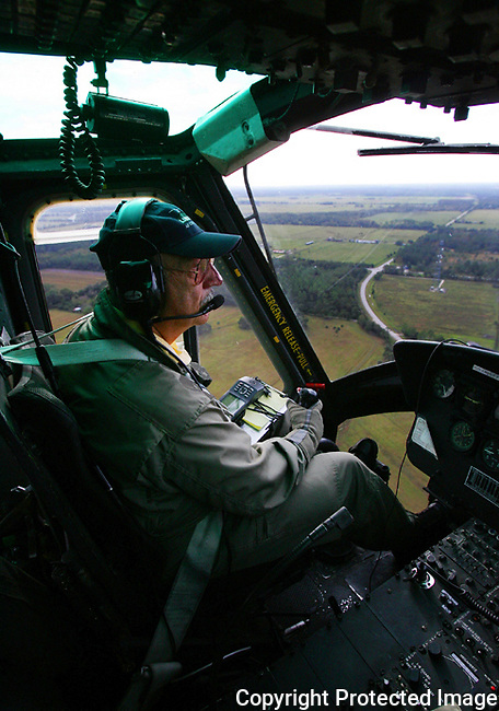 "Flight instructor Jerry Borchin at the controls of a Bell UH-1 ""Huey"" helicopter during a search-and-rescue training flight over Flagler County, Tuesday, Nov. 16, 2004.  After more than 30 years, the Vietnam war veteran, now retired and living in Port Orange, is back in the helicopter that served so well in that conflict.(Brian Myrick)"