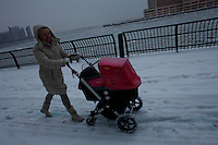 A woman walks by the Hudson River shore in Jersey City, as winter storm hits the tri-state area causing significant delays at airports in the region. Last month was coldest February in New York City since 1869. Mar 01,2015. Kena Betancur/VIEWpress.