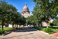 Capitol of Texas Great Walk - The Texas Capitol in downtown Austin through the trees from the South view with this wonderful blue sky and pattern limestone walkway which is called the Great Walk . The Capitol of Texas is located in downtown at Congress ave facing toward south congress from this view. The Capitol building is an impresses building with it large dome done in the Renaissance Revival architecture with the red granite from Granite Mountain and the rest of the capital in Oak Hill Limestone.