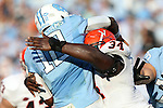 24 October 2015: UNC's Marquise Williams (12) is hit by Virginia's Kwontie Moore (34) as he releases the ball. The University of North Carolina Tar Heels hosted the University of Virginia Cavaliers at Kenan Memorial Stadium in Chapel Hill, North Carolina in a 2015 NCAA Division I College Football game. UNC won the game 26-13.