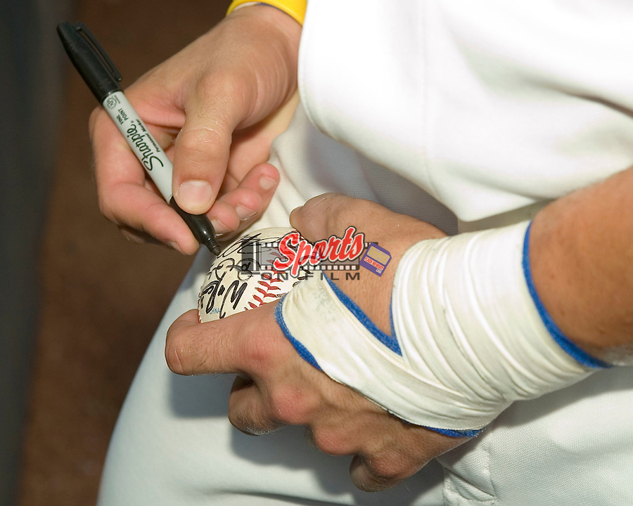 Team USA catcher J.P. Arencibia (44) autographs a baseball for a fan at Durham Bulls Athletic Park in Durham, NC, Friday, July 21, 2006.