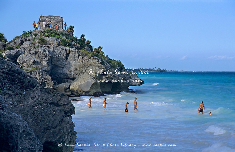 Bathers on the beach at the foot of an ancient Mayan site in Tulum, Quintana Roo, Yucatán, Mexico.