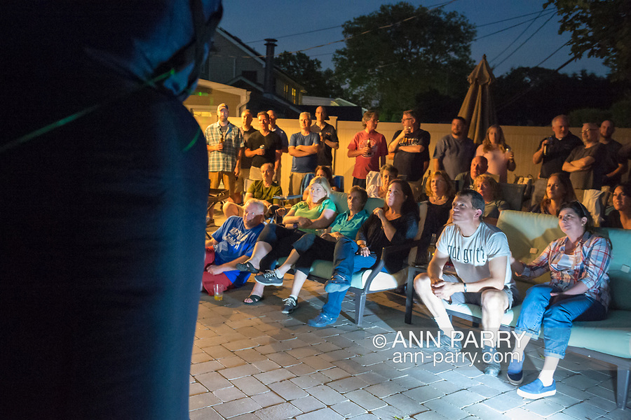 """Merrick, New York, USA. 11th June 2017.  """"American Grit"""" TV contestant CHRIS EDOM (at bottom right, wearing white GOT GRIT? T-shirt), 48, sits with his wife, JOAN EDOM, of Merrick, as they host backyard Viewing Party for Season 2 premiere. Edom family and neighbors watched Episode 1 of FOX network reality television series that Sunday night on a big screen (at left) outdoors. Edom was last contestant picked for a team."""