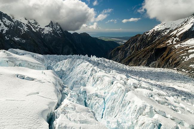 Downstream view into valley across seracs of Main Icefall on Franz Josef Glacier and toward  Tasman Sea on horizon, Westland Tai Poutini National Park, West Coast, UNESCO World Heritage Area, New Zealand, NZ