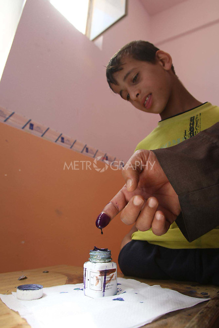 NAJAF, IRAQ: A voter dips their finger ink after voting in Najaf...On March 7th, 2010, Iraq held nationwide parliamentary elections.