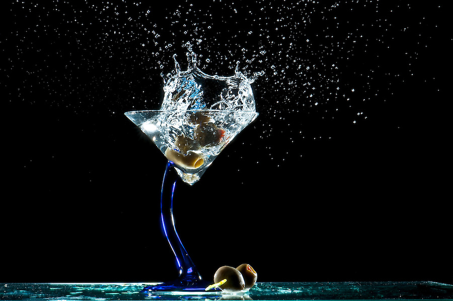 Splash of olives into a glass of martini.