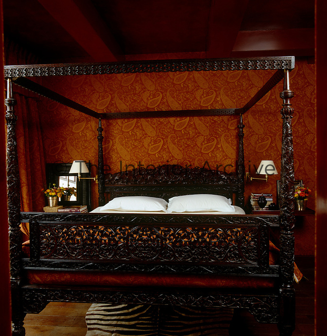 A large carved four-poster bed dominates this room which is decorated with an orange paisley fabric