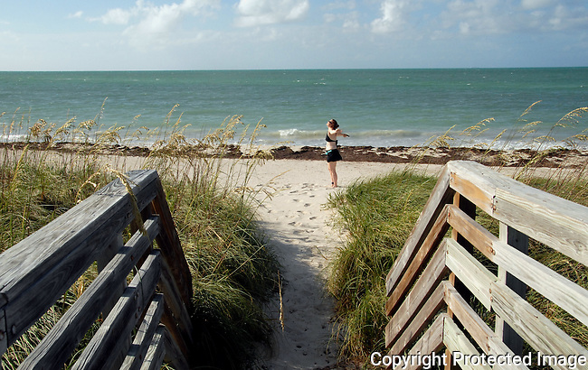 woman stands on sand with arms outstretched just beyond the wooden pathway leading to Silver Spur Beach at Bahia Honda State Park, Florida Keys