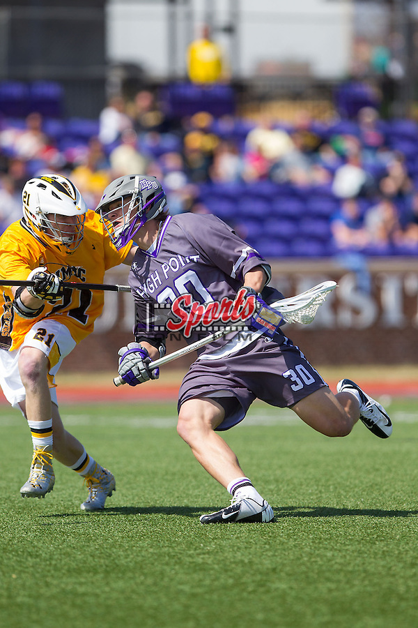 Tyler Cook (30) of the High Point Panthers is checked by Seth Mackin (21) of the UMBC Retrievers at Vert Track, Soccer & Lacrosse Stadium on March 15, 2014 in High Point, North Carolina.  The Panthers defeated the Retrievers 17-15.   (Brian Westerholt/Sports On Film)